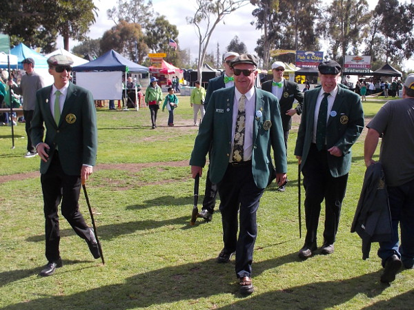 Irish gentlemen in green jackets cross the grass at the west end of Balboa Park.