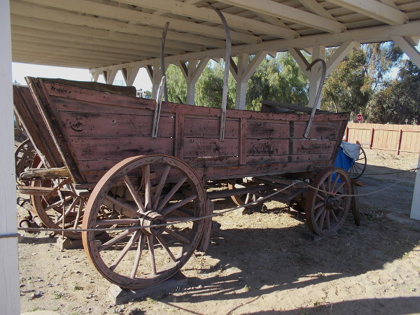 An old covered wagon on display behind Seeley Stable. They were typically sturdy farm wagons with a canvas top. Covered wagons were used on trail drives and cross-country treks.