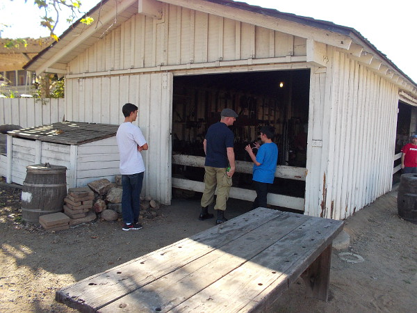 Some park visitors look into the small blacksmith building.