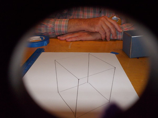 When I peered at the image through a hole near the end of the string, I saw a perfect cube! Cool!