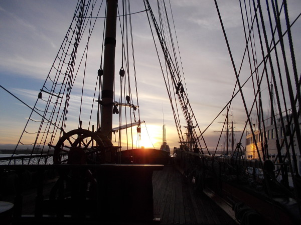 Sun falls behind picturesque deck and rigging of HMS Surprise.