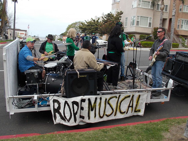 Some musicians get ready on a trailer beside the parade route. They're advertising Rope the Musical.
