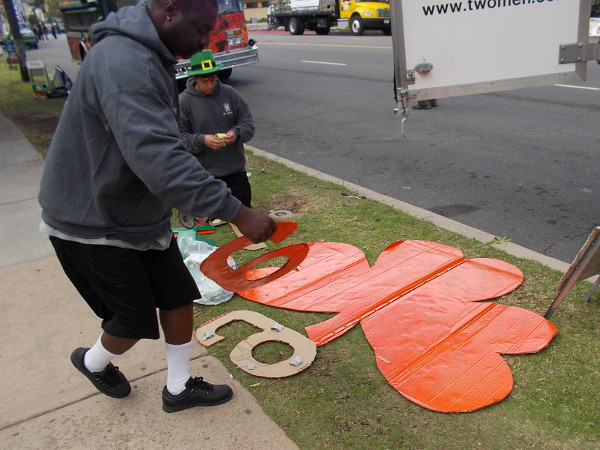Folks prepare their float for the St. Patrick's Day Parade. It will feature a big orange shamrock.