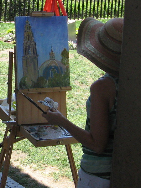An artist paints the California Tower from the edge of the San Diego Museum of Art's grassy May S. Marcy Sculpture Garden.