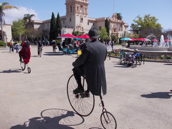 A pair of penny-farthing riders head through the Plaza de Panama in Balboa Park on a sunny San Diego day.