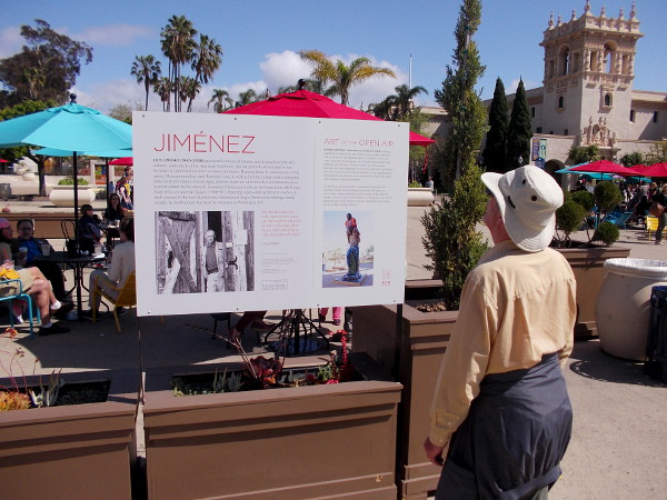 Visitor to Balboa Park reads sign describing an outdoor sculpture recently installed in the Plaza de Panama, part of the Art of the Open Air exhibit.