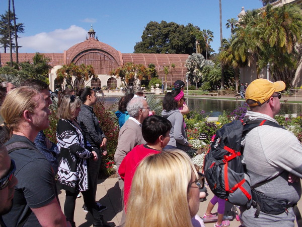 A large crowd watches some street entertainment. The Botanical Building rises in the background.