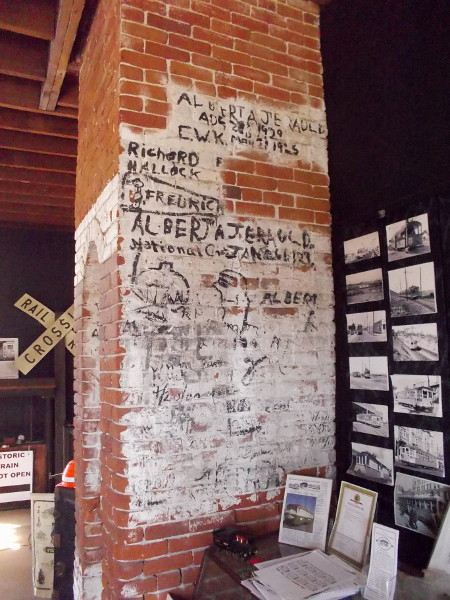 Faded writing on the brick fireplace recalls when the eventually abandoned depot was used as a restaurant. Black panels on the walls cover graffiti.