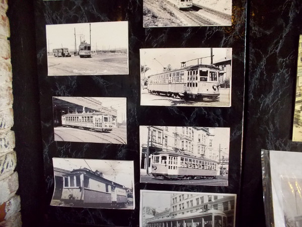 One section of a wall has lots of photos of vintage streetcars and trolleys.