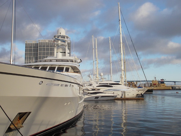 White superyachts docked behind the San Diego Convention Center are bathed in late afternoon light.