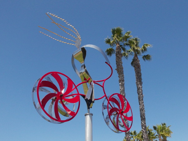 A steel bicyclist with wildly blowing hair flies through the blue sky past some Southern California palm trees!