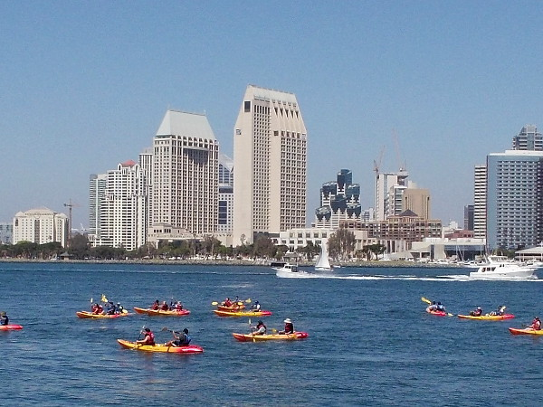 That big group of kayakers is rowing toward the Coronado Ferry Landing. The Manchester Grand Hyatt towers rise across the bay.