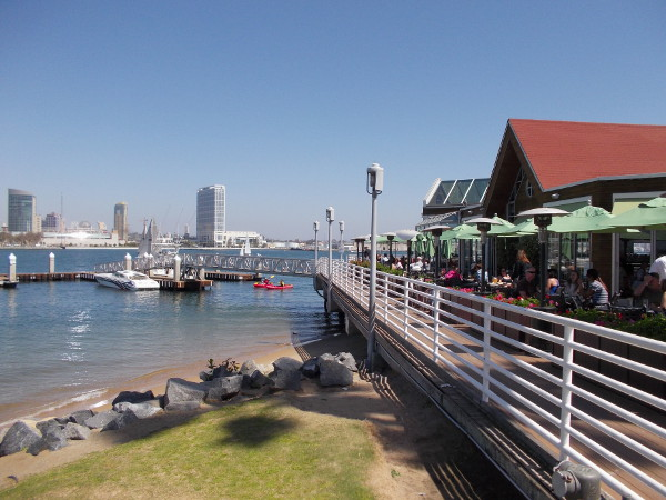 Some kayakers are passing the dock at Peohe's, as outside diners watch. Night views of downtown San Diego lit up across the water are awesome.