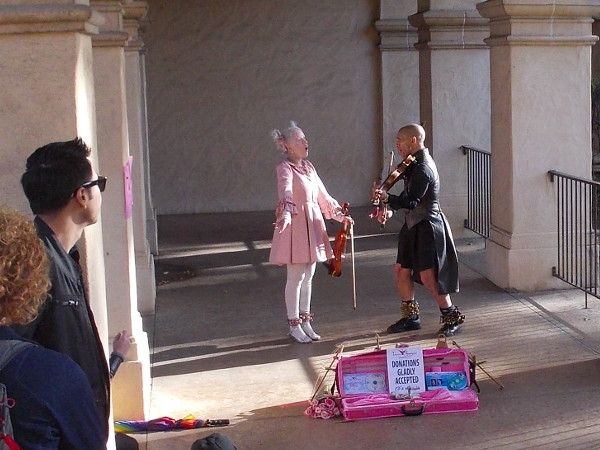 Victorian street act wows a small crowd within colonnade of the Casa del Prado.
