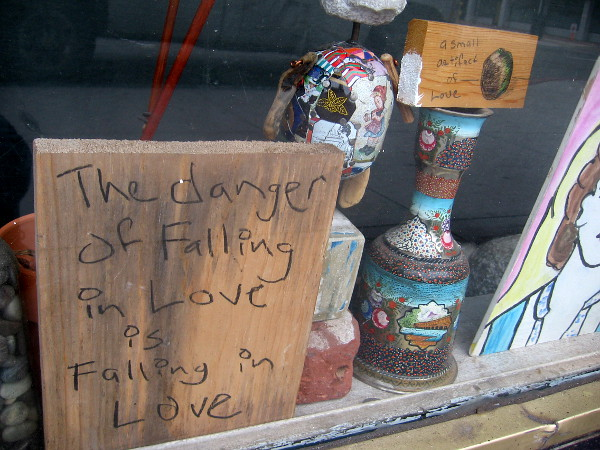 A small handwritten sign seen in a San Diego window. The danger of falling in love is falling in love.