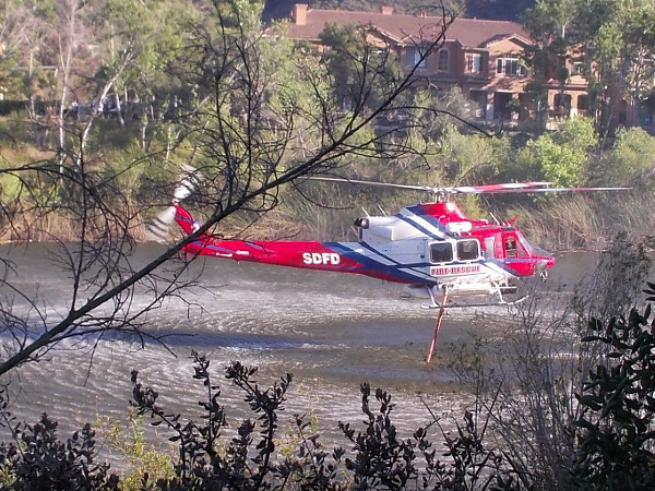One of the San Diego Fire Department's two firefighting helicopters fills it water tank using a hose lowered into the San Diego River in Mission Valley.