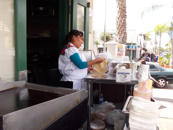 Making fresh tortillas for people walking down the sidewalk in front of Cafe Coyote. Eat these hot with melted butter and you're in heaven.