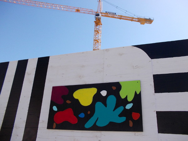 A big construction crane in downtown San Diego rises over globs of color.