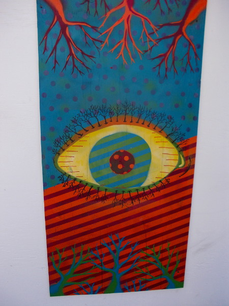 A psychedelic, tree-lined eyeball between colorful barren branches.