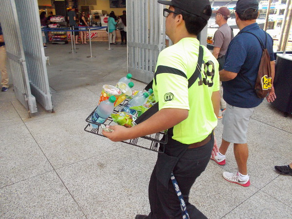 A busy vendor walks about with drinks and snacks.