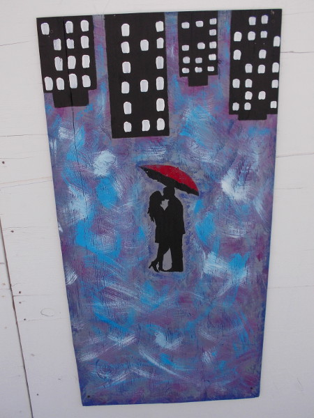 A couple, a red umbrella, and city lights.