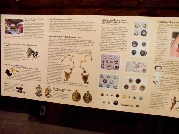 Sign describes additional historical finds, including buttons, toys, harmonicas, slate board and pencils, lice combs, toothbrush handles, shoe parts, medal rosary and religious medallions.