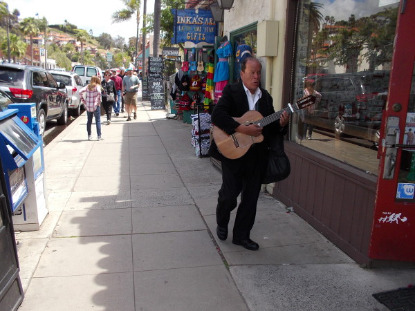 A guitarist walks down a sidewalk in Old Town. You'll find plenty of music and life up and down San Diego Avenue.