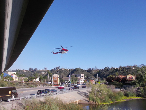 A wildfire must be nearby because here comes a firefighting helicopter swooping rapidly down over Mission Center Road toward a wide spot in the San Diego River!