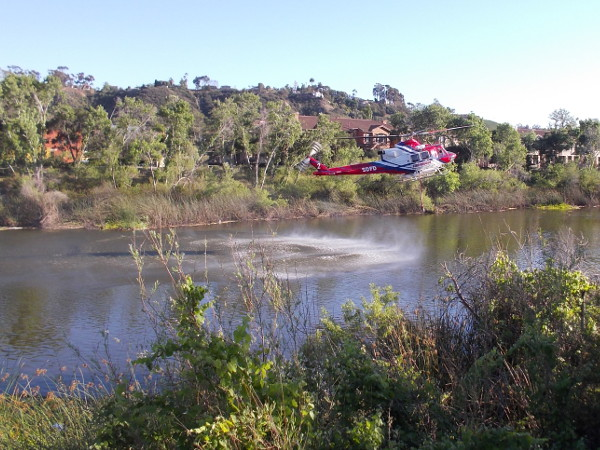 The air from the rotor blades causes spray to fly up from the surface of the San Diego River. Several joggers and walkers on the nearby paths stopped to watch.