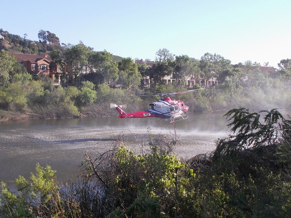 The long hose quickly sucks a good quantity of water from the river. The pilot is highly skilled, hovering the helicopter above the water, steady as a rock.