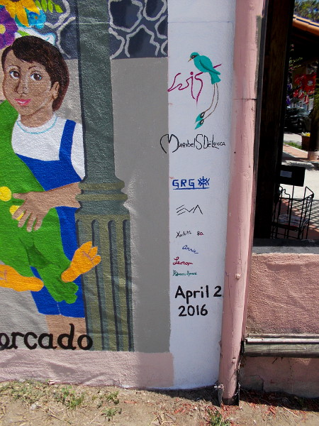 Un dia de Mercado was completed on April 2, 2016. It was painted by several talented artists. Their signatures are evident in this photo. New colorful urban art in Normal Heights!