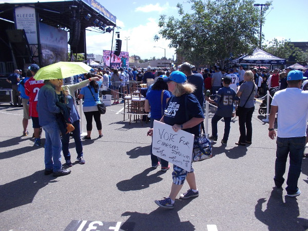 Someone in the gathering crowd holds a Vote for Chargers Stadium sign.