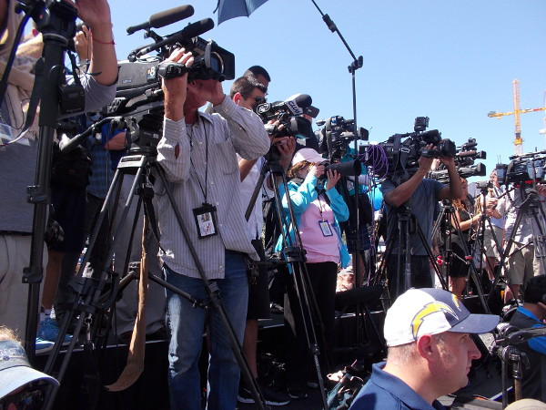 Television news cameras and media photographers jam together to capture the Chargers' downtown stadium petition publicity event.