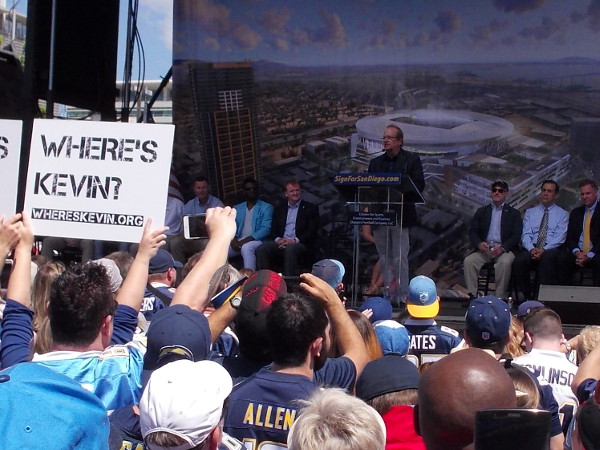 Dean Spanos, team president and CEO of the National Football League's San Diego Chargers team takes the stage. Pre-made signs intended to shame Mayor Faulconer rise in unison.