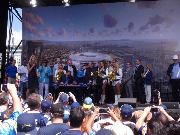 Several super fans take part in a ceremonial first signing on stage with the various dignitaries.