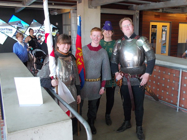 Performers in medieval chain mail and shining breastplate armor pose inside the main entrance of the San Diego Central Library downtown!