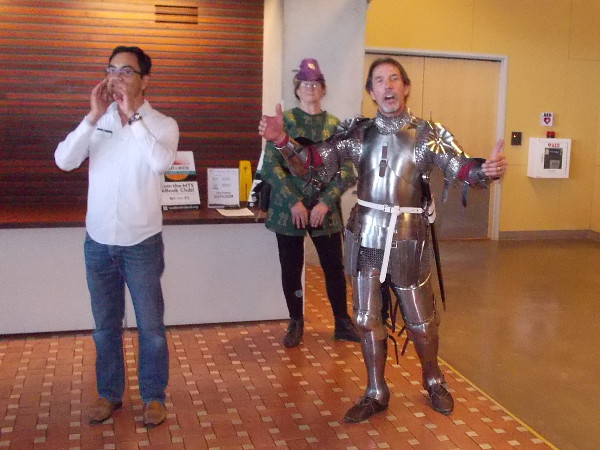 Henry V inspires his troops in the Age of Chivalry, while historical commentary is provided in a modern library. The performance was part of an ongoing summer-long First Folio celebration of Shakespeare.