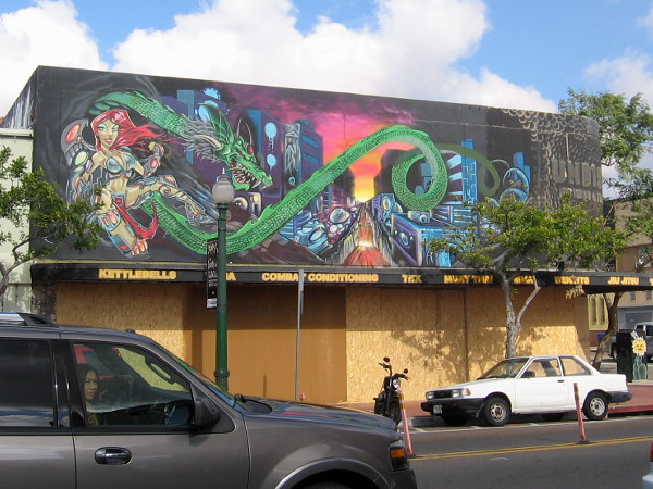 Bold image along the roof of another building. A female warrior, a green dragon and a brilliant city scene.