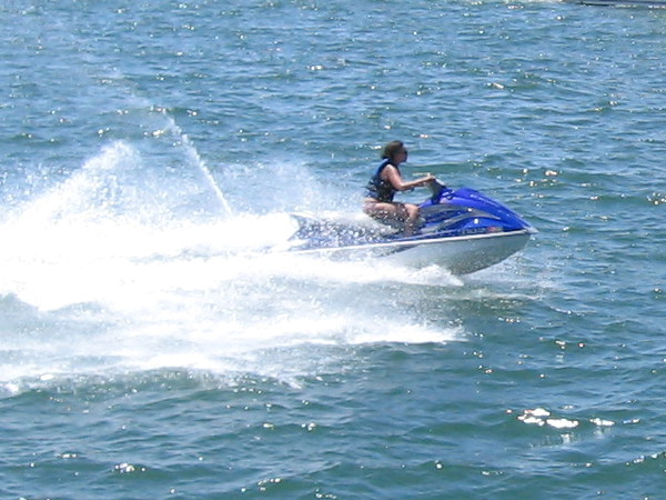 Someone zooms by riding a bucking water scooter over the sparkling blue water.