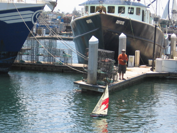 Someone relaxes on a spring Sunday by maneuvering a remote control model sailboat in Tuna Harbor. Another cool sight along San Diego's always lively Embarcadero.