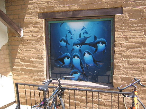 Fun marine artwork depicts a pod of dolphins in the ocean. A window of the Wyland Galleries in Seaport Village.