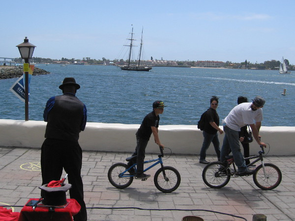 A street magician, cyclists, and the Californian tall ship out on San Diego Bay.