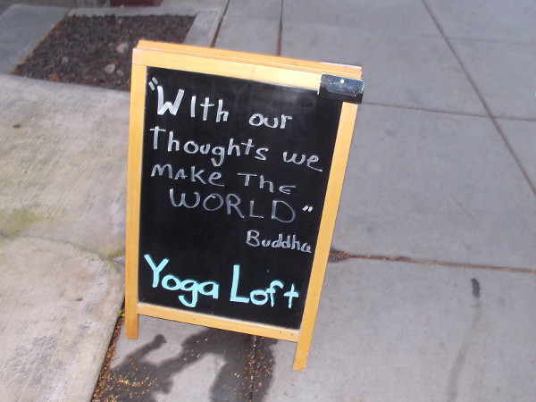 Sign on San Diego sidewalk. With our thoughts we make the world. Buddha.