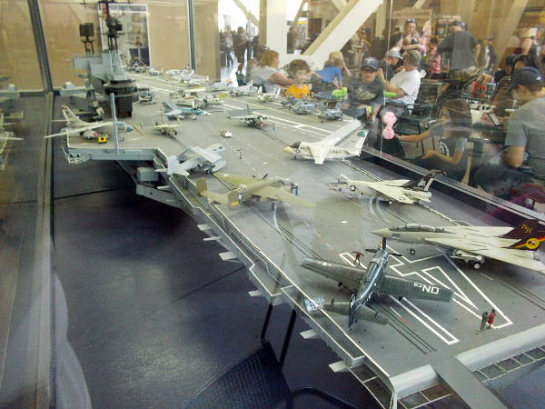 Many different model aircraft are parked on the flight deck of the enormous model aircraft carrier.