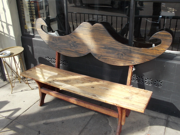 A bench shaped like a mustache. A fun sight in front of a barber shop.