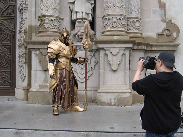 A cool knight in golden armor poses for a photo shoot in front of Balboa Park's ornate Museum of Man facade.