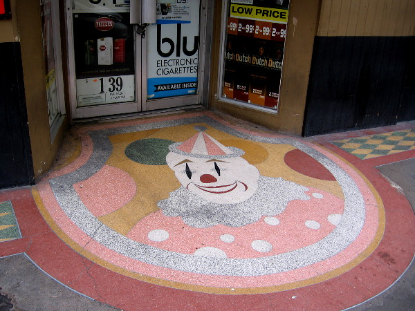 A happy clown face decorates the Fourth Avenue sidewalk, a block north of Broadway near the center of San Diego.