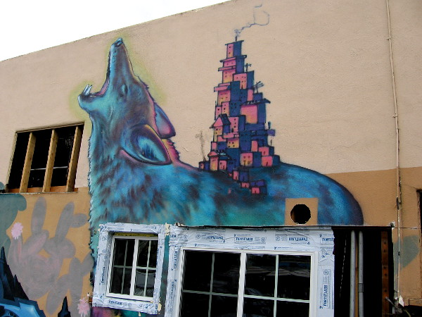 Houses appear to be stacked on the back of a howling wolf! One of several fantastic images on a building that is being renovated in North Park.