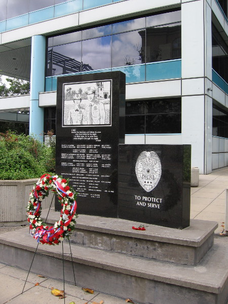 Wreath in front of San Diego Police Headquarters' Wall of Honor, remnant of a recent memorial ceremony. The wall is inscribed with the names of all police officers killed in the line of duty since 1913.