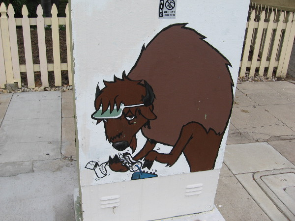 A utility box with a bit of funny street art. This tired buffalo appears to be crunching some numbers.